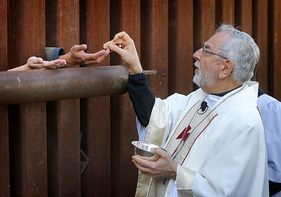 FOR USE AS DESIRED, YEAR END PHOTOS - FILE - Most Reverend Gerald F. Kicanas, Bishop of Tucson, offers communion to people on the Mexican side of the international border, Tuesday, April 1, 2014, in Nogales, Ariz. Kicanas and Boston Archdiocese Cardinal Sean O'Malley, along with several Bishops who serve along the U.S./Mexico border, were visiting the border town to bring awareness to immigration reform and to remember those who have died trying to cross the border in years past. (AP Photo/Matt York, File)