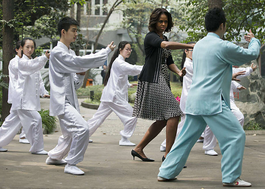FOR USE AS DESIRED, YEAR END PHOTOS - FILE - U.S. first lady Michelle Obama practices tai chi with students at Chengdu No.7 High School in Chengdu in southwest China's Sichuan province Tuesday, March 25, 2014. (AP Photo/Andy Wong, File)