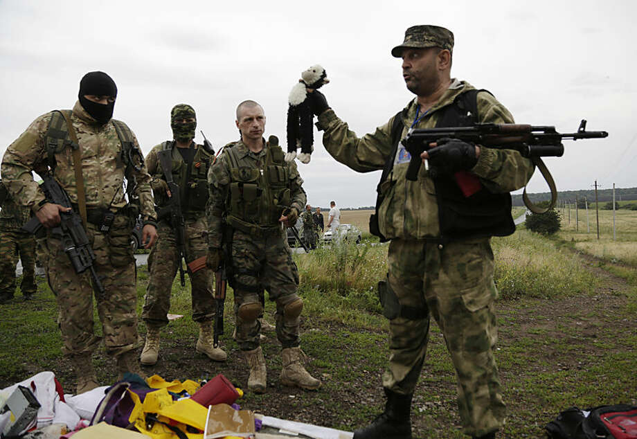 FOR USE AS DESIRED, YEAR END PHOTOS - FILE - A pro-Russian fighter holds up a toy found among the debris at the crash site of a Malaysia Airlines jet near the village of Hrabove, Friday, July 18, 2014. Emergency workers, police officers and even off-duty coal miners spread out across the sunflower fields and villages of eastern Ukraine, searching the wreckage of a Malaysia Airlines jet shot down as it flew high above the country's battlefield. The attack killed 298 people from nearly a dozen nations. (AP Photo/Dmitry Lovetsky, File)