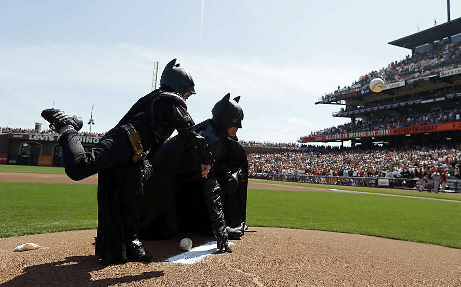 FOR USE AS DESIRED, YEAR END PHOTOS - FILE - Miles Scott, left, dressed as Batkid, throws the ceremonial first pitch next to Batman before an opening day baseball game between the San Francisco Giants and the Arizona Diamondbacks in San Francisco, Tuesday, April 8, 2014. On Nov. 15, 2013, Scott, a Northern California boy with leukemia, fought villains and rescued a damsel in distress as a caped crusader through The Greater Bay Area Make-A-Wish Foundation. (AP Photo/Eric Risberg, Pool, File)
