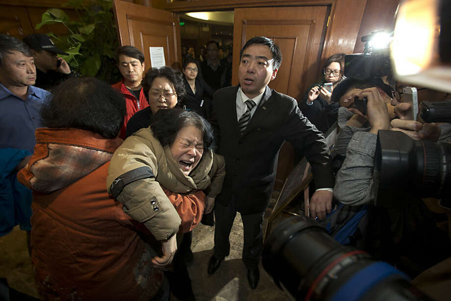 FOR USE AS DESIRED, YEAR END PHOTOS - FILE - A relative of Chinese passengers aboard Malaysia Airlines MH370 grieves after being told of the latest news in Beijing, China, Monday, March 24, 2014. (AP Photo/Ng Han Guan, File)