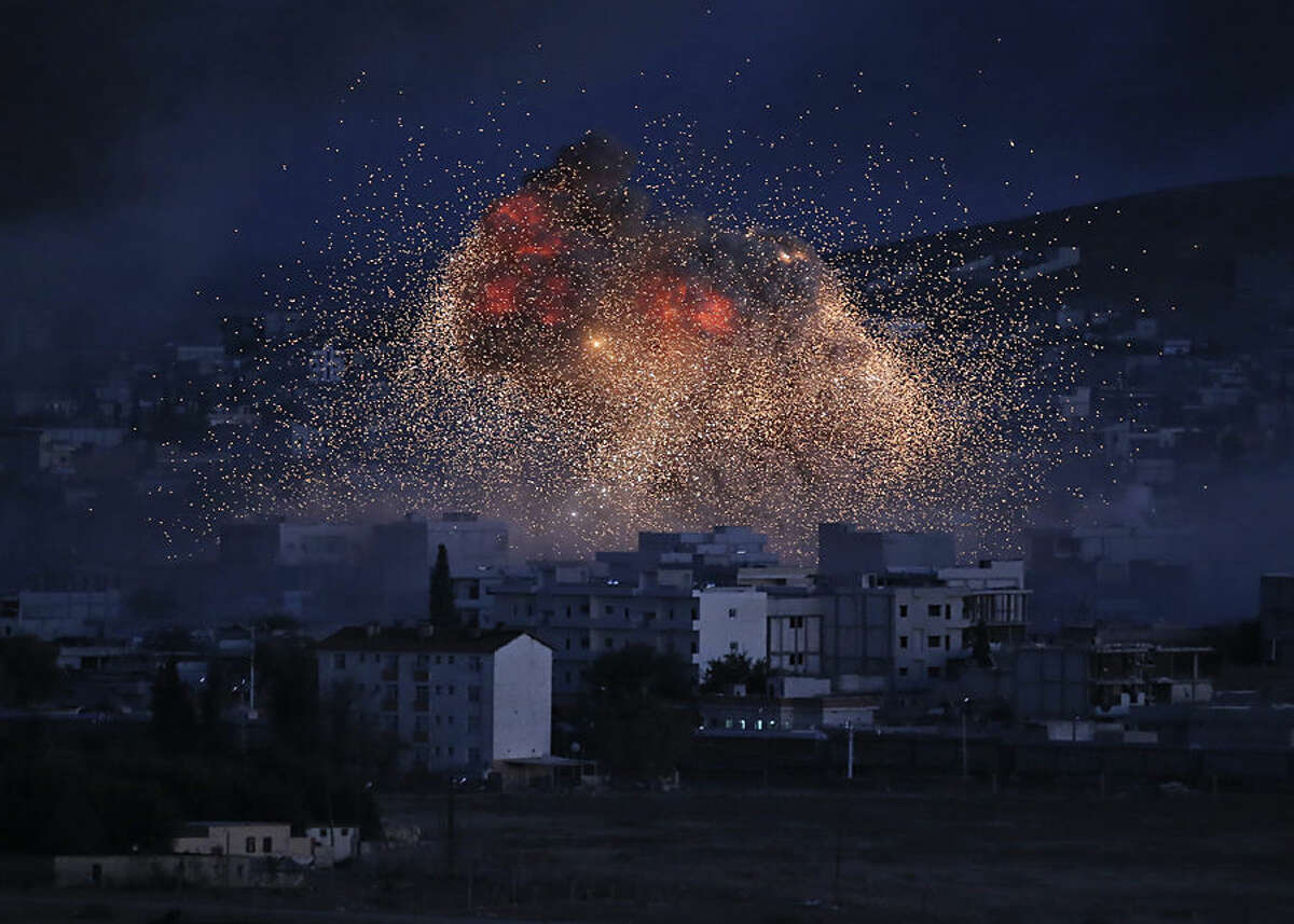 FOR USE AS DESIRED, YEAR END PHOTOS - FILE - Thick smoke and flames from an airstrike by the U.S.-led coalition rise in Kobani, Syria, as seen from a hilltop on the outskirts of Suruc, at the Turkey-Syria border, Monday, Oct. 20, 2014. Kobani, also known as Ayn Arab, and its surrounding areas, has been under assault by extremists of the Islamic State group since mid-September and is being defended by Kurdish fighters. (AP Photo/Lefteris Pitarakis, File)