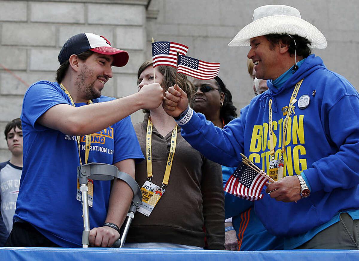 FOR USE AS DESIRED, YEAR END PHOTOS - FILE - Holding American flags, Boston Marathon bombing survivor Jeff Bauman, left, bumps fists with Carlos Arredondo near the finish line of the the 118th Boston Marathon, Monday, April 21, 2014, in Boston. (AP Photo/Elise Amendola, File)