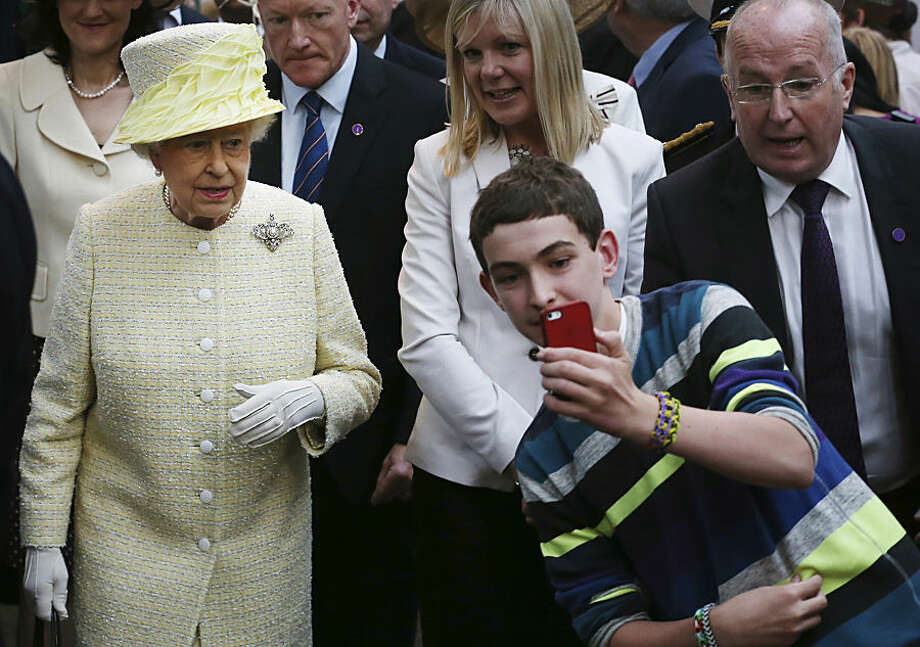 FOR USE AS DESIRED, YEAR END PHOTOS - FILE - A local youth takes a selfie photograph in front of Queen Elizabeth II during a visit to St George's indoor market on in Belfast Tuesday June 24, 2014. The Queen is on a 3 day visit to Northern Ireland. (AP Photo/Peter Macdiarmid, File Pool)