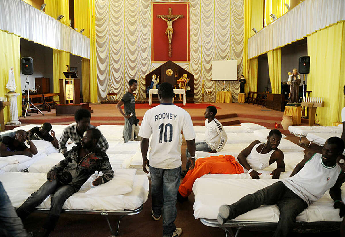FOR USE AS DESIRED, YEAR END PHOTOS - FILE - In this picture taken Sunday, June 15, 2014, migrants from Africa are temporarily sheltered in the Catholic church of St. Curato D'Ars in Palermo, Sicily, Italy. The Italian coast guard and navy have rescued more than 300 migrants whose boats ran into trouble in the Mediterranean Sea and recovered the bodies of 10 migrants whose dinghy had overturned. (AP Photo/Alessandro Fucarini, File)
