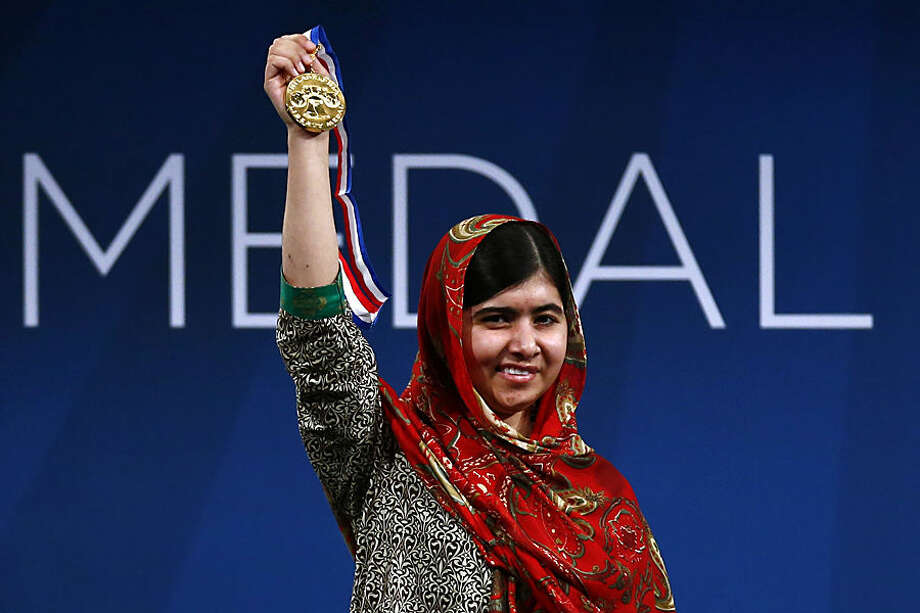 FOR USE AS DESIRED, YEAR END PHOTOS - FILE - Malala Yousafzai holds up her Liberty Medal during a ceremony at the National Constitution Center, Tuesday, Oct. 21, 2014, in Philadelphia. The honor is given annually to an individual who displays courage and conviction while striving to secure liberty for people worldwide. (AP Photo/Matt Rourke, File)