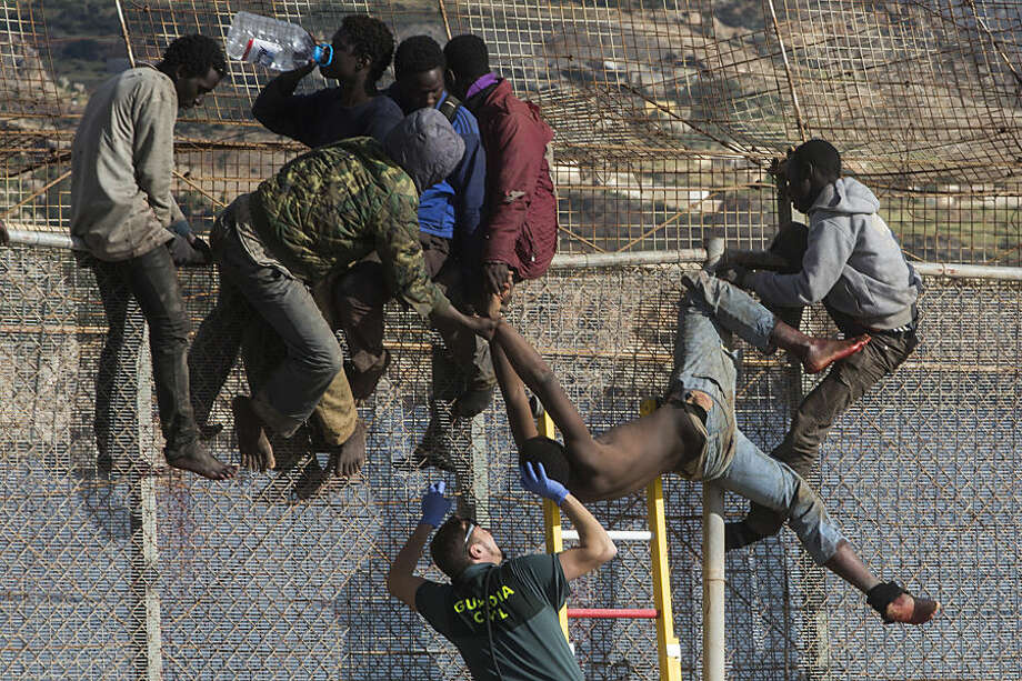 FOR USE AS DESIRED, YEAR END PHOTOS - FILE - A sub-Saharan migrant is helped by a Spanish Guardia Civil officer after he fainted on top of a metallic fence that divides Morocco and the Spanish enclave of Melilla, Thursday, April 3, 2014. Spanish and Moroccan police have thwarted a fresh attempt by dozens of African migrants to try to scale border fences to enter the Spanish enclave of Melilla. Thousands of sub-Saharan migrants seeking a better life in Europe are living illegally in Morocco and regularly try to enter Melilla in the hope of later making it to mainland Spain. (AP Photo/Santi Palacios, File)