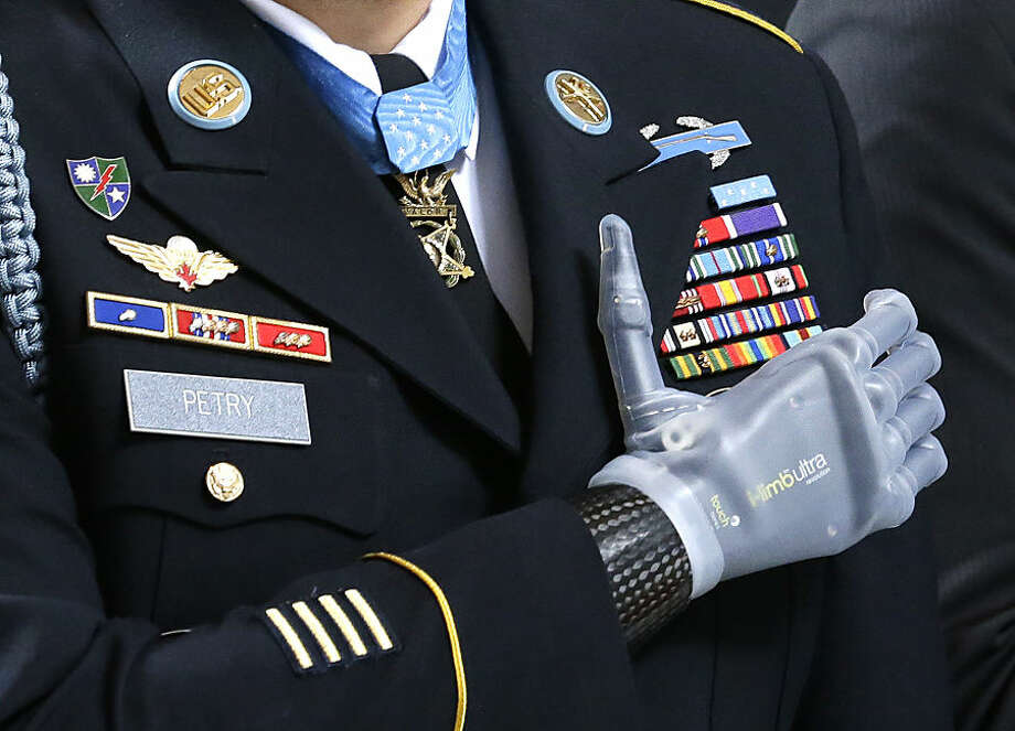 "FOR USE AS DESIRED, YEAR END PHOTOS - FILE - Medal of Honor recipient Sgt. 1st Class Leroy Petry stands with his prosthetic hand over his heart, wearing his Medal of Honor during the ""Pledge of Allegiance"" at the Capitol in Olympia, Wash. on Wednesday, April 2, 2014, during a ceremony to honor him and other recipients of the Medal of Honor from Washington state. Petry lost his hand in 2008 when an enemy grenade he was throwing away from fellow soldiers detonated while in combat in Afghanistan. (AP Photo/Ted S. Warren, File)"