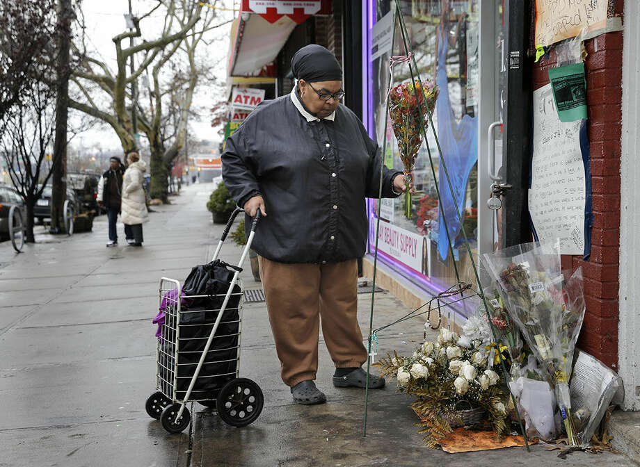 A woman, who did not want to give her name, places flowers at a memorial for Eric Garner near the site of his death in the borough of Staten Island Wednesday, Dec. 3, 2014., in New York. A grand jury is deciding whether to indict a New York City police officer in the chokehold death of Garner. (AP Photo/Seth Wenig)
