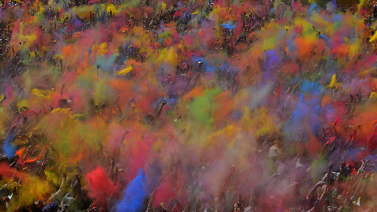 FOR USE AS DESIRED, YEAR END PHOTOS - FILE - Visitors of the Holi Festival of Colours throw special colored powders in the air in Barcelona, Spain, Sunday, April 6, 2014. The festival is fashioned after the Hindu spring festival Holi, which is mainly celebrated in the north and east of India. (AP Photo/Manu Fernandez, File)