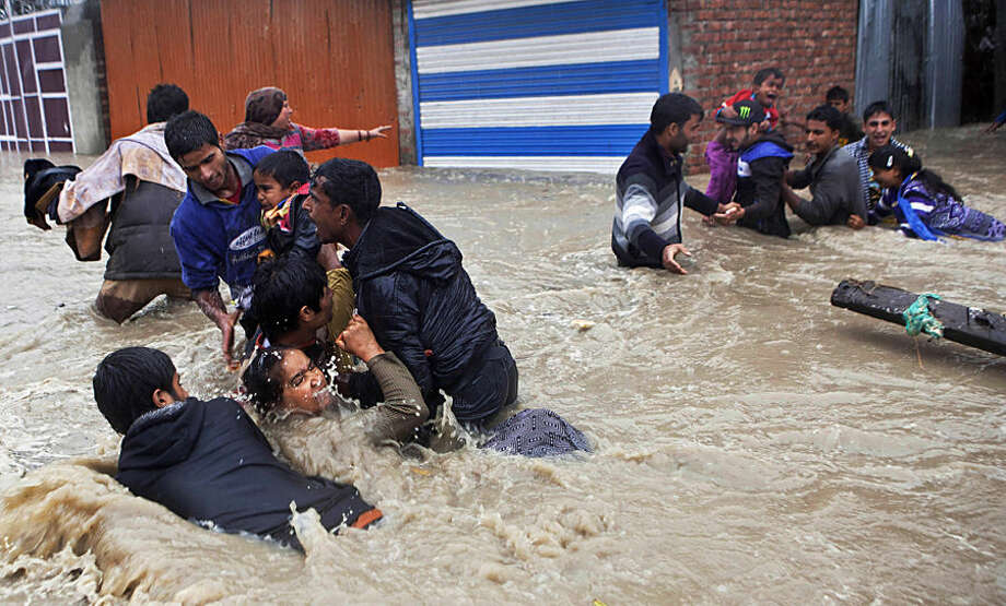 FOR USE AS DESIRED, YEAR END PHOTOS - FILE - Kashmiri residents wade through floodwaters in Srinagar, India, Thursday, Sept. 4, 2014. At least 100 villages across the Kashmir valley were flooded by overflowing lakes and rivers. (AP Photo/Dar Yasin, File)
