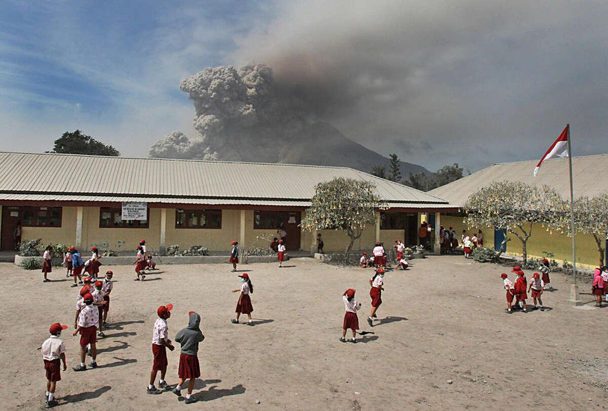 FOR USE AS DESIRED, YEAR END PHOTOS - FILE - Students play in their school yard as Mount Sinabung erupts in Sukandebi, North Sumatra, Indonesia, Thursday, Jan. 16, 2014. (AP Photo/Binsar Bakkara, File)
