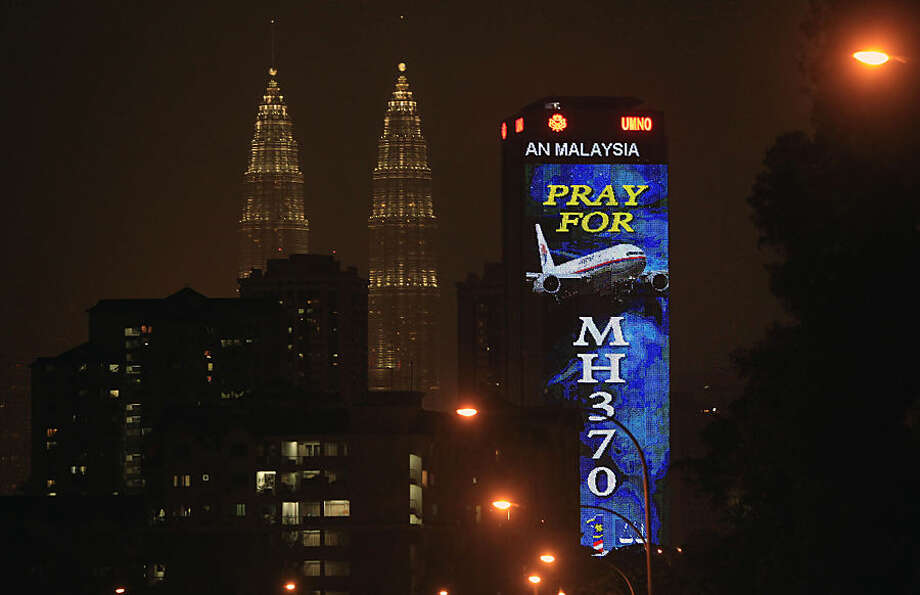 "FOR USE AS DESIRED, YEAR END PHOTOS - FILE - An office building is illuminated with LED lights displaying ""Pray for MH370"" next to Malaysia's landmark Petronas Twin Towers in Kuala Lumpur, Malaysia, Wednesday, March 19, 2014. (AP Photo/Lai Seng Sin, File)"