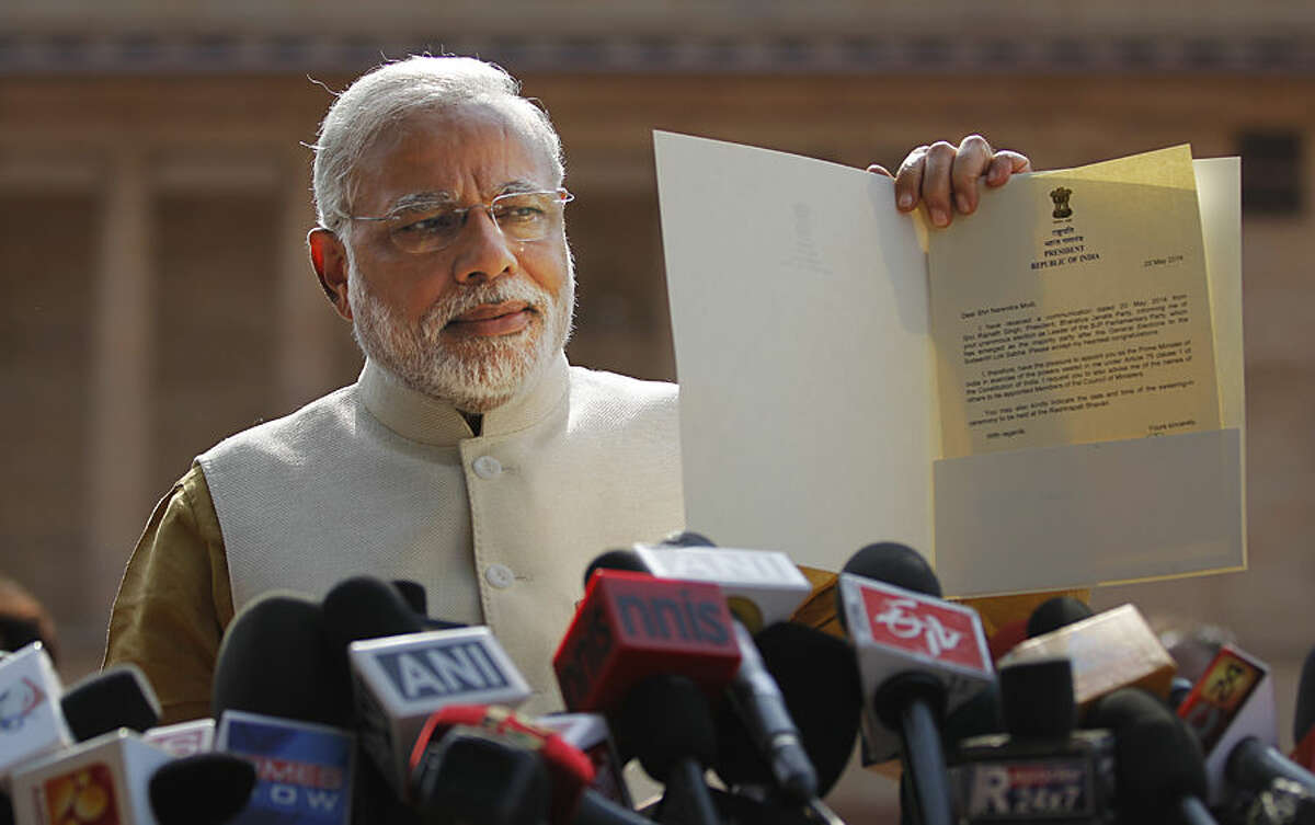 FOR USE AS DESIRED, YEAR END PHOTOS - FILE - India's next prime minister and Hindu nationalist Bharatiya Janata Party (BJP) leader Narendra Modi displays the letter from the Indian President inviting him to form the new government, outside the Presidential Palace in New Delhi, India, Tuesday, May 20, 2014. Modi met with President Pranab Mukherjee after he was formally chosen by his party as the next prime minister, just days after a resounding victory in national elections. (AP Photo/Altaf Qadri, File)