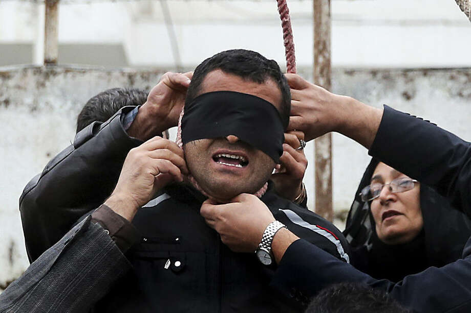 FOR USE AS DESIRED, YEAR END PHOTOS - FILE - This picture provided by ISNA, a semi-official news agency, taken on Tuesday, April 15, 2014 shows Maryam Hosseinzadeh, right, and her husband Abdolghani, left, removing the noose from the neck of blindfolded Bilal who was convicted of murdering their son Abdollah in the northern city of Nour, Iran. Bilal who was convicted of killing Abdollah Hosseinzadeh, was pardoned by the victim's family moments before being executed. (AP Photo/ISNA, Arash Khamoushi, File)