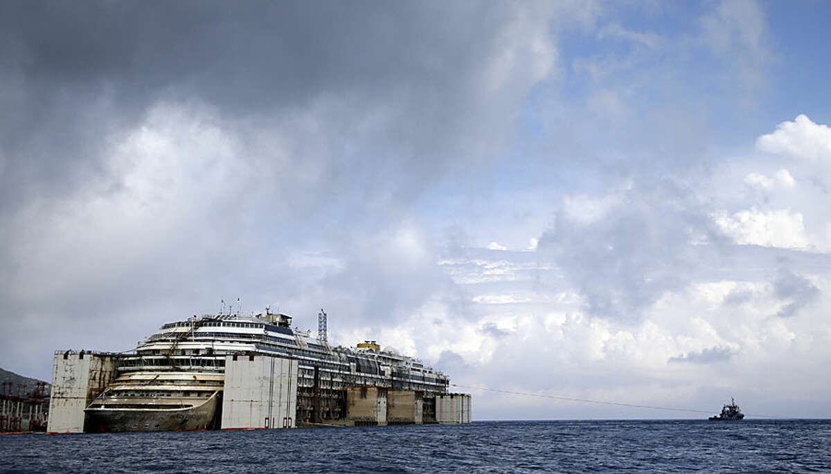 FOR USE AS DESIRED, YEAR END PHOTOS - FILE - The wreck of the luxury cruise ship Costa Concordia is held up by giant tanks as tug boats surround it in the final stages of the refloating phase before being towed to the Italian port of Genoa, in the tiny Tuscan island of Isola del Giglio, Italy, Monday, July 21, 2014. (AP Photo/Gregorio Borgia, File)