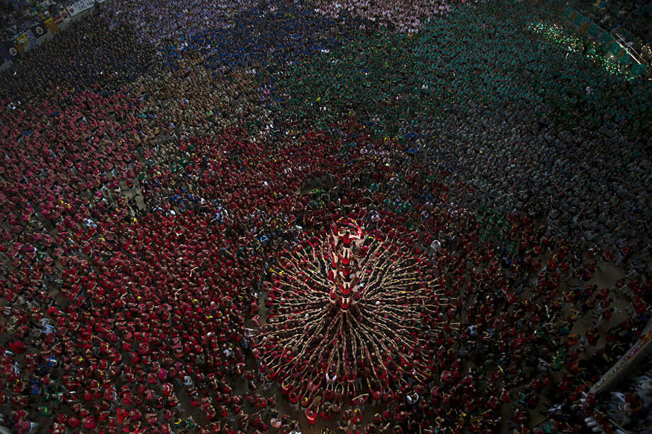 FOR USE AS DESIRED, YEAR END PHOTOS - FILE - Members of the Castellers Joves Xiquets de Valls try to complete their human tower during the 25th Human Tower Competition in Tarragona, Spain, on Sunday, Oct. 5, 2014. The tradition of building human towers, or castells, dates back to the 18th century and takes place during festivals in Catalonia, where colles, or teams, compete to build the tallest and most complicated towers. The structure of the castells varies depending on their complexity. A castell is considered completely successful when it is loaded and unloaded without falling apart. The highest castell in history was a 10 floor structure with 3 people in each floor. In 2010 castells were declared by UNESCO one of the Masterpieces of the Oral and Intangible Heritage of Humanity. (AP Photo/Emilio Morenatti, File)