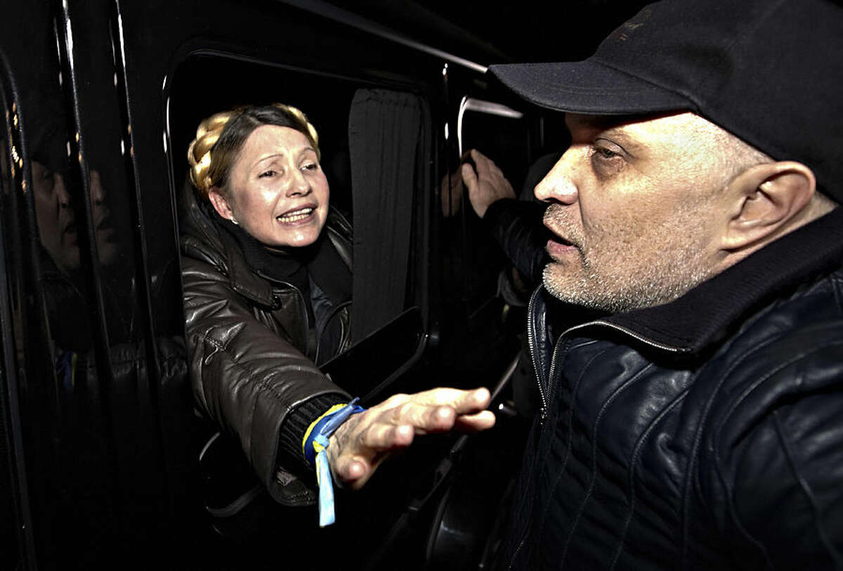 FOR USE AS DESIRED, YEAR END PHOTOS - FILE - Former Ukrainian Prime Minister Yulia Tymoshenko is greeted by supporters shortly after being freed from prison in Kharkiv, Ukraine, Saturday, Feb. 22, 2014. (AP Photo/Sergey Kozlov, File)