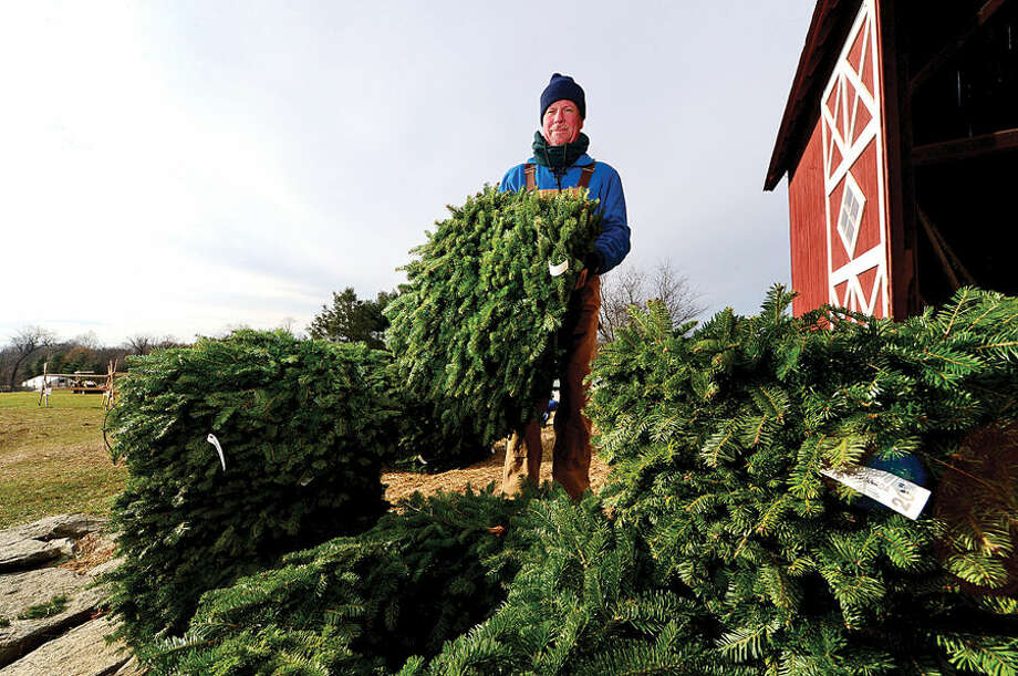 Workers with Ambler Farm, Lee Horticultural Services, Tall Trees landscaping, Earthscapes and Wilton Lawn Services, including neighbor and former board member Mark Keough, unload nearly 400 Christmas trees and over 250 wreaths for the farm's annual Christmas tree sale.