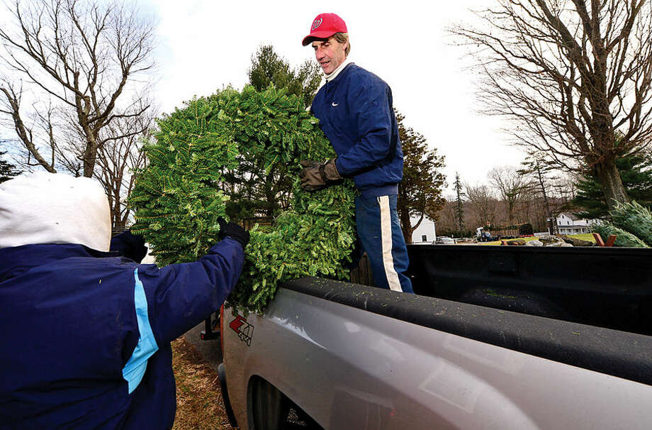 Workers with Ambler Farm, Lee Horticultural Services, Tall Trees Landscaping, Earthscapes, and Wilton Lawn Services owner John Morin, unload nearly 400 Christmas trees and over 250 wreaths for the farm's annual Christmas tree sale.