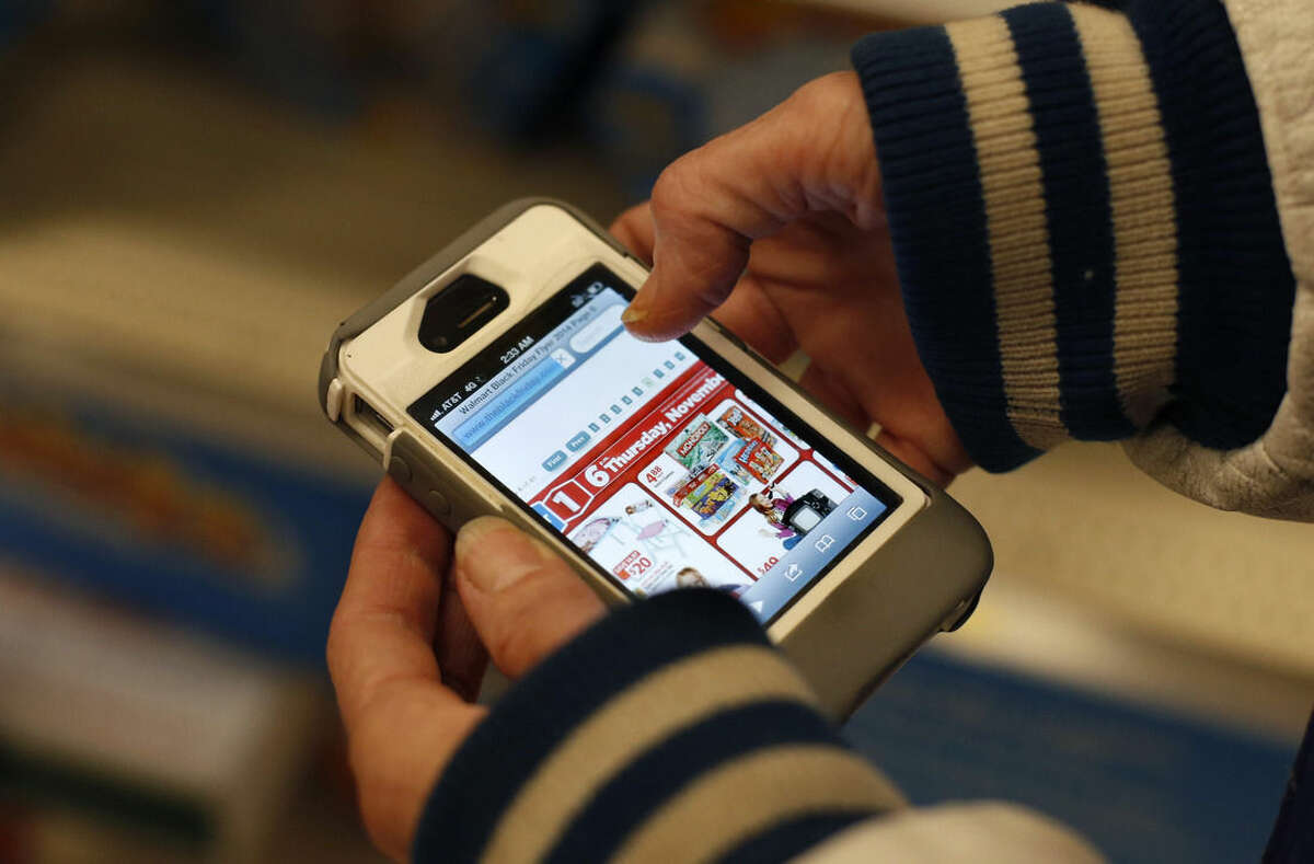 A Target shopper uses her iPhone to compare prices at Wal-Mart while shopping after midnight on Black Friday, Nov. 28, 2014, in South Portland, Maine. (AP Photo/Robert F. Bukaty)