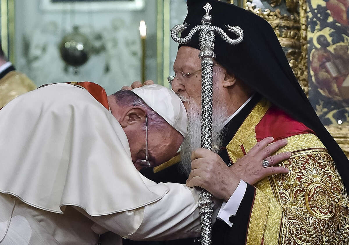 In this photo provided by Vatican newspaper L'Osservatore Romano, Ecumenical Patriarch Bartholomew I, right, kisses Pope Francis' head during an ecumenical prayer at the Patriarchal Church of St. George in Istanbul, Saturday, Nov. 29, 2014. The two major branches of Christianity represented by Bartholomew and Francis split in 1054 over differences on the power of the papacy. The two spiritual heads will participate in an ecumenical liturgy and sign a joint declaration in the ongoing attempt to reunite the churches. (AP Photo/L'Osservatore Romano, ho)