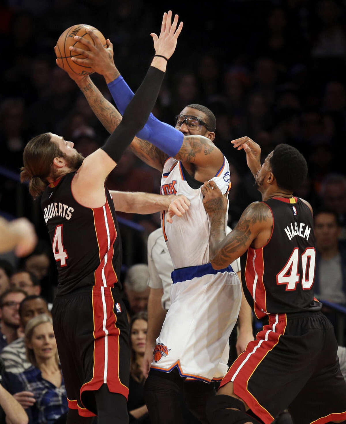 New York Knicks' Amar'e Stoudemire, center, tries to pass around Miami Heat's Josh McRoberts, left, and Udonis Haslem during the first half of an NBA basketball game, Sunday, Nov. 30, 2014, in New York. (AP Photo/Seth Wenig)