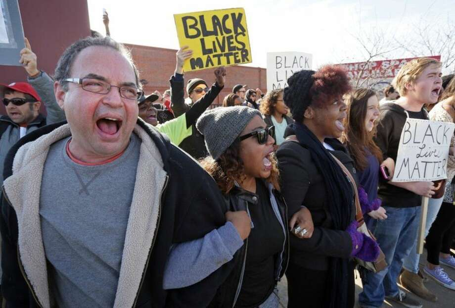 """Black lives matter"" shout protesters Daniel Conford, left, Tracy Parks, Ashley Carter, Judy Lucas and Luke Davis, right as they all link arms and face off to police at during a demonstration along Eager Road on Saturday, Nov. 29, 2014. (AP Photo/St. Louis Post-Dispatch, David Carson)"