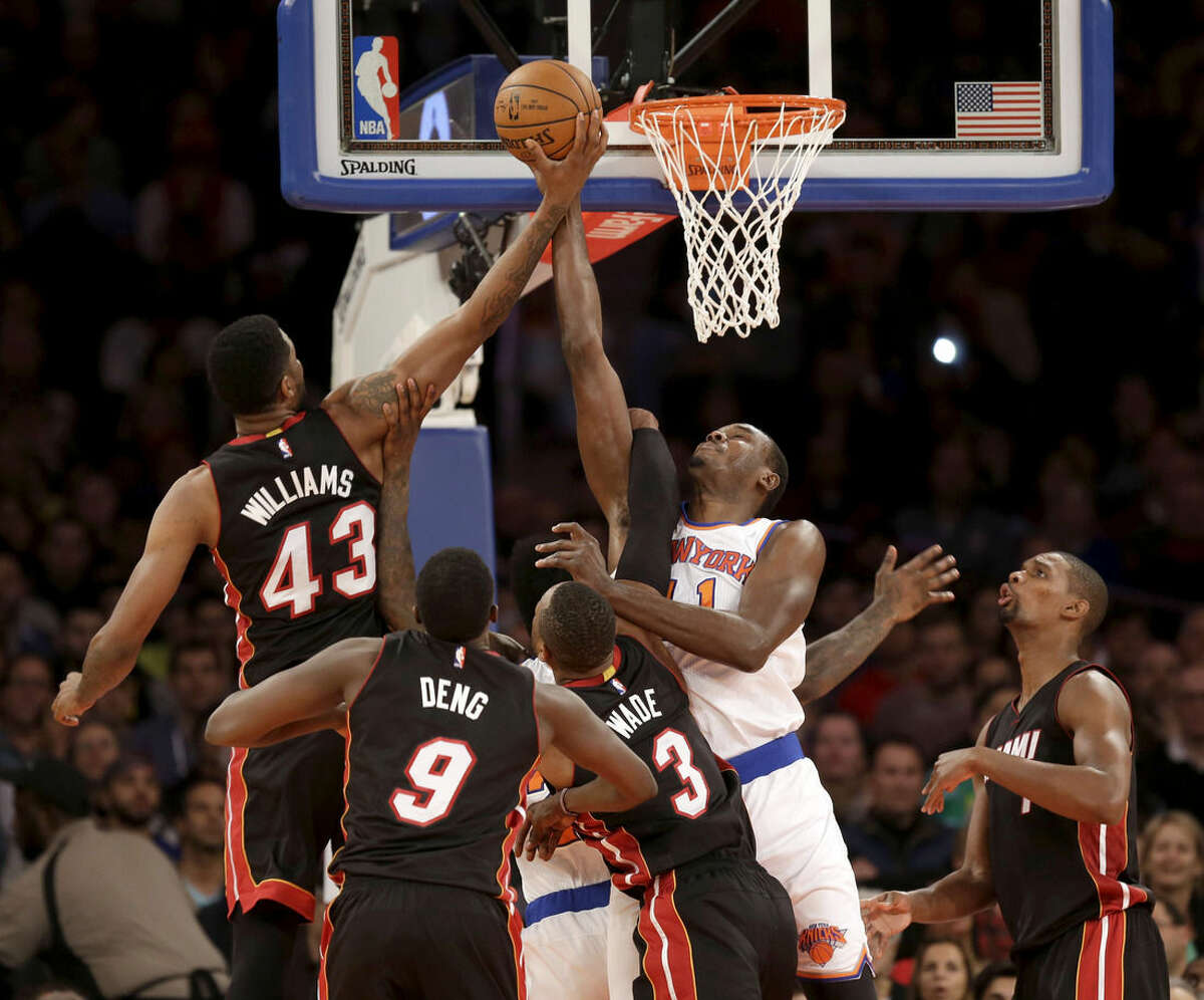Miami Heat's Shawne Williams, left, and New York Knicks' Samuel Dalembert, second from right, fight for a rebound during the first half of an NBA basketball game, Sunday, Nov. 30, 2014, in New York. (AP Photo/Seth Wenig)