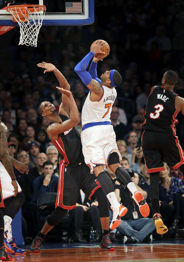 Miami Heat's Chris Bosh, left, fouls New York Knicks' Carmelo Anthony, center, as he goes up for a shot during the first half of an NBA basketball game, Sunday, Nov. 30, 2014, in New York. (AP Photo/Seth Wenig)