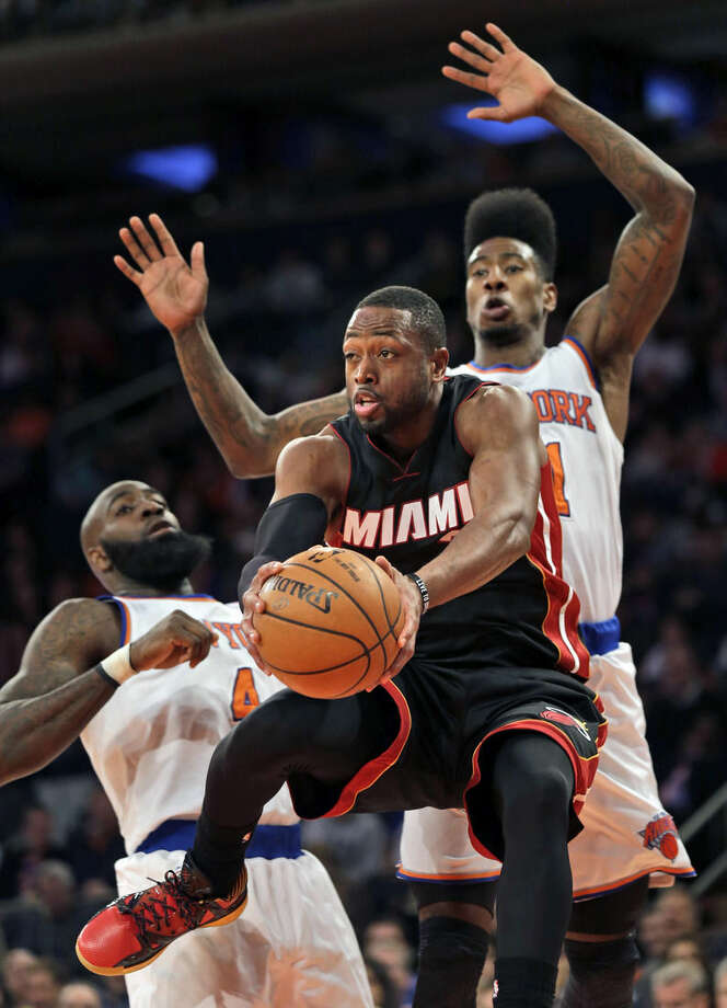 Miami Heat's Dwyane Wade, center, passes the ball while New York Knicks' Quincy Acy, left, and Iman Shumpert defend during the first half of an NBA basketball game, Sunday, Nov. 30, 2014, in New York. (AP Photo/Seth Wenig)