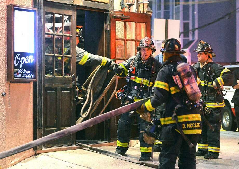 Hour Photo/Alex von Kleydorff Norwalk Firefighters get a hose inside B.J. Ryan's on Main St. Monday evening in response to a fire in the kitchen of the restaurant