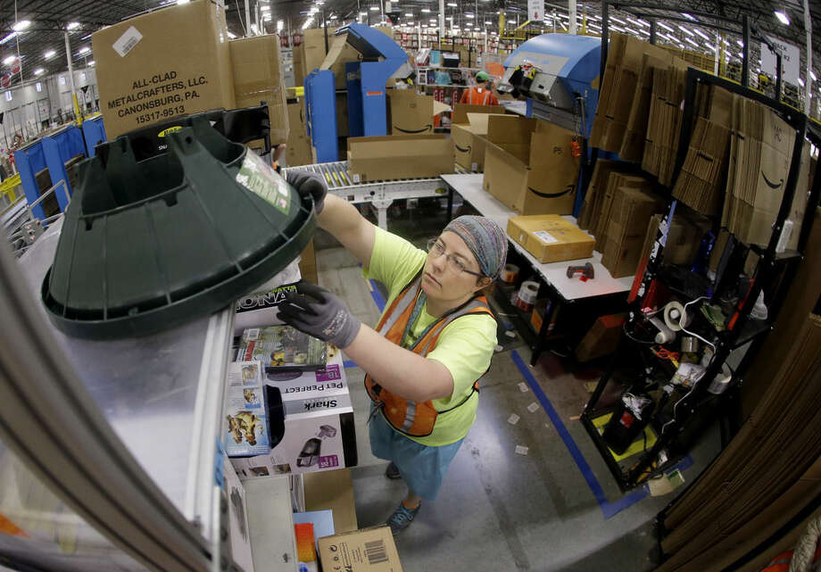 Ashley Merritt packs an order for shipping at the Amazon fulfillment center in Lebanon, Tenn. on Monday, Dec. 1, 2014. Retailers rolled out discounts and free shipping deals on Cyber Monday, with millions of Americans expected to log on and shop on their work computers, laptops and tablets after the busy holiday shopping weekend. (AP Photo/Mark Humphrey)