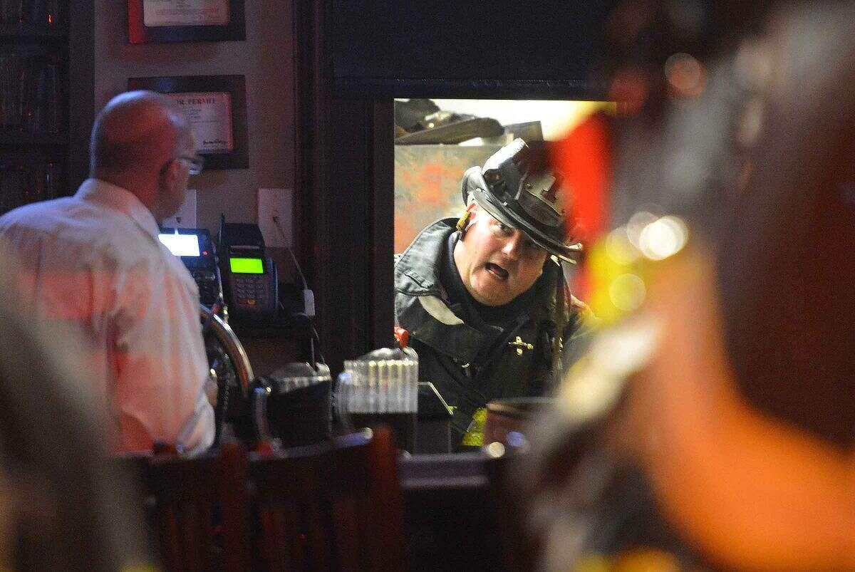 Hour Photo/Alex von Kleydorff. Norwalk Firefighters work to extinguish a kitchen fire at B.J. Ryan's on Monday night