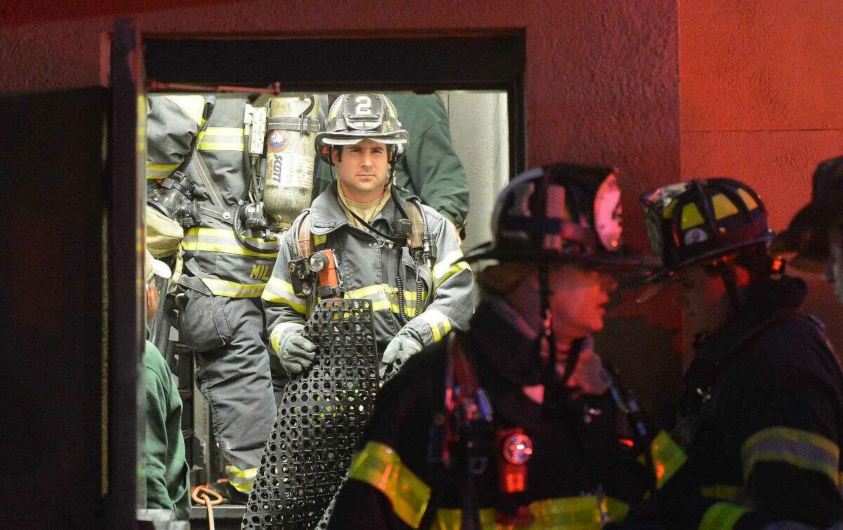 Hour Photo/Alex von Kleydorff Norwalk Firefighters carry kitchen items and floor mat's out the back door while responding to B.J.Ryan's on Main st. Monday evening for a fire in the kitchen