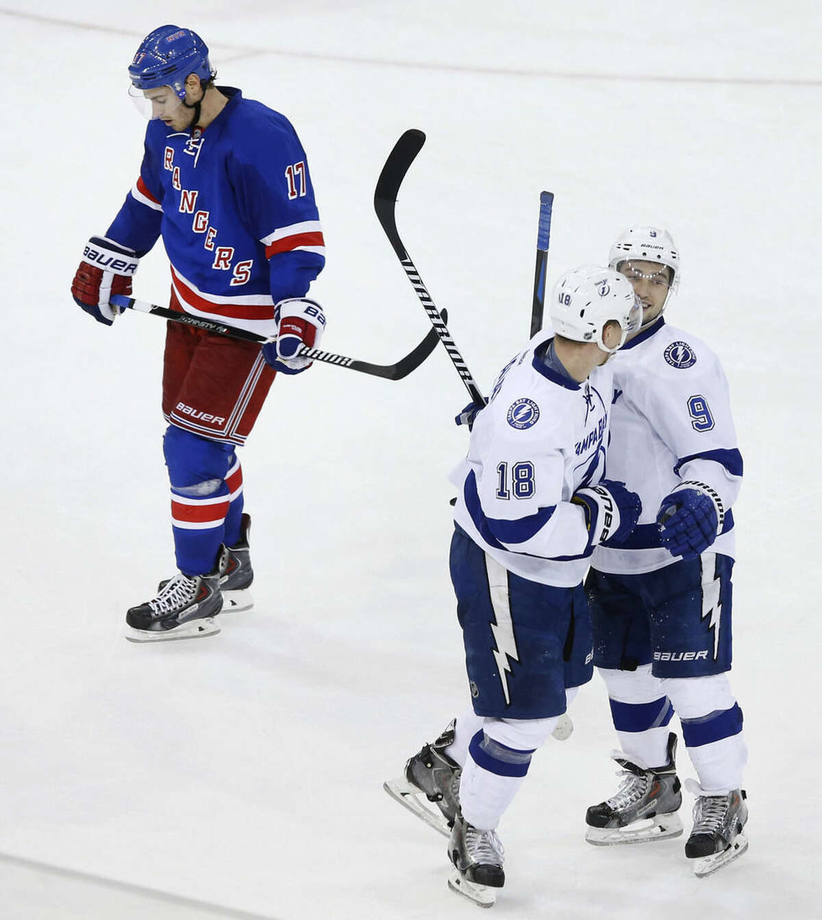 New York Rangers' John Moore (17) skates by as Tampa Bay Lightning's Ondrej Palat (18), of Czech Republic, celebrates with teammate Tyler Johnson (9) after scoring an empty net goal during the third period of an NHL hockey game Monday, Dec. 1, 2014, in New York. Tampa Bay won 6-3. (AP Photo/Jason DeCrow)