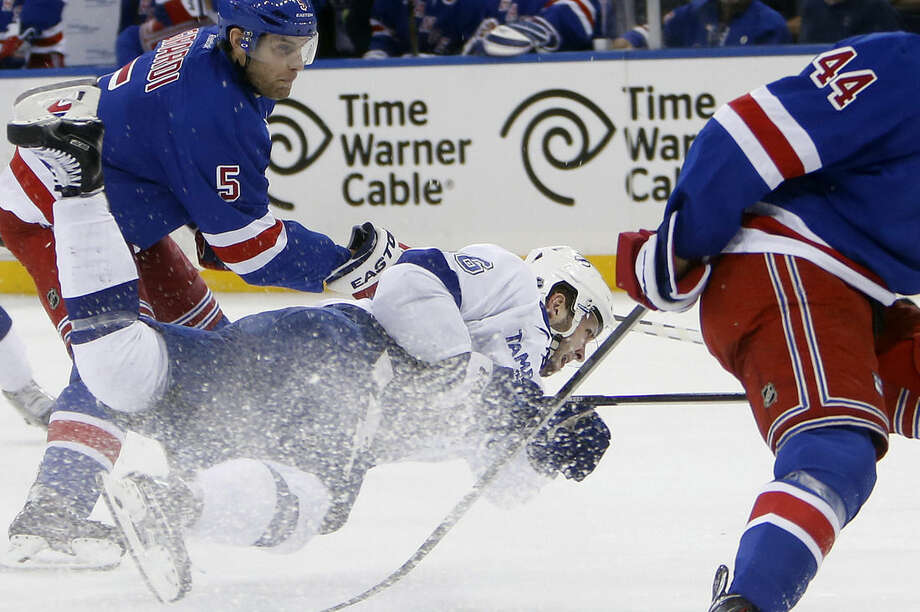 Tampa Bay Lightning's Nikita Kucherov, center, of Russia, falls to the ice as he sends the puck away from New York Rangers' Dan Girardi (5) during the first period of an NHL hockey game Monday, Dec. 1, 2014, in New York. (AP Photo/Jason DeCrow)