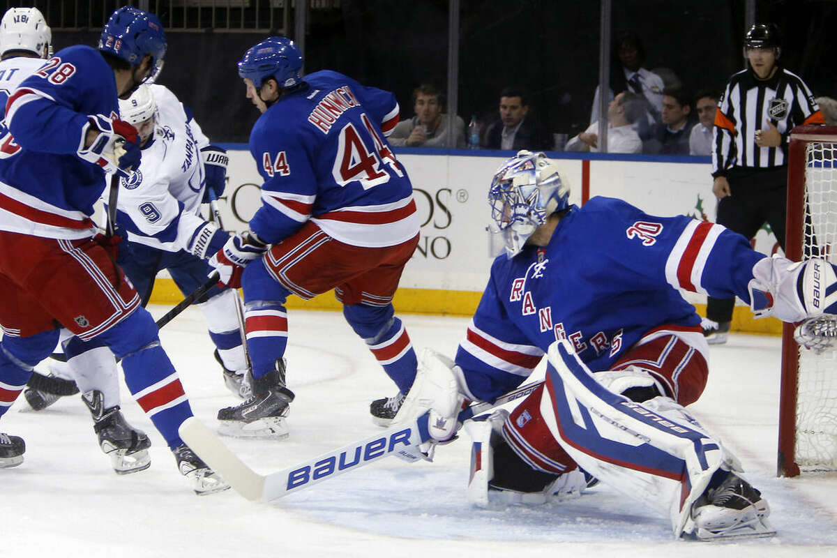 Tampa Bay Lightning's Tyler Johnson (9) scores against New York Rangers goalie Henrik Lundqvist (30), of Sweden, during the first period of an NHL hockey game Monday, Dec. 1, 2014, in New York. (AP Photo/Jason DeCrow)