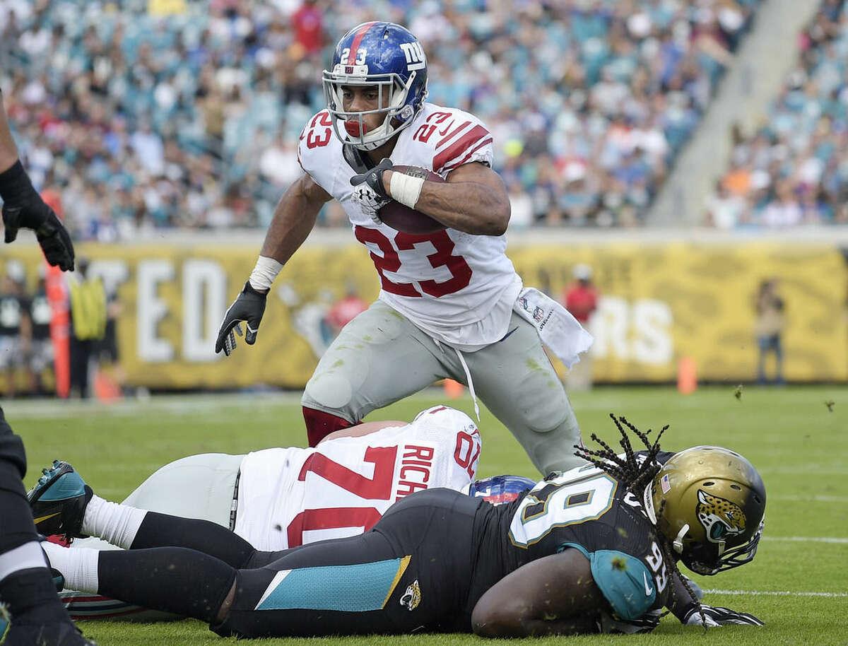 New York Giants running back Rashad Jennings (23) runs for a 2-yard touchdown against the Jacksonville Jaguars during the first half of an NFL football game in Jacksonville, Fla., Sunday, Nov. 30, 2014. (AP Photo/Phelan M. Ebenhack)