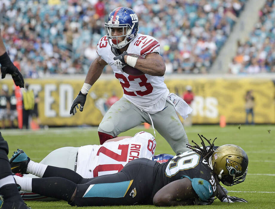 New York Giants running back Rashad Jennings (23) runs for a 2-yard touchdown against the Jacksonville Jaguars during the first half of an NFL football game in Jacksonville, Fla., Sunday, Nov. 30, 2014. (AP Photo/Phelan M. Ebenhack)