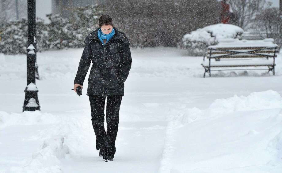 Hour Photo/Alex von Kleydorff Carolanne Browne makes her way through a very quiet Town Green in Wilton Center during Monday's snowstorm