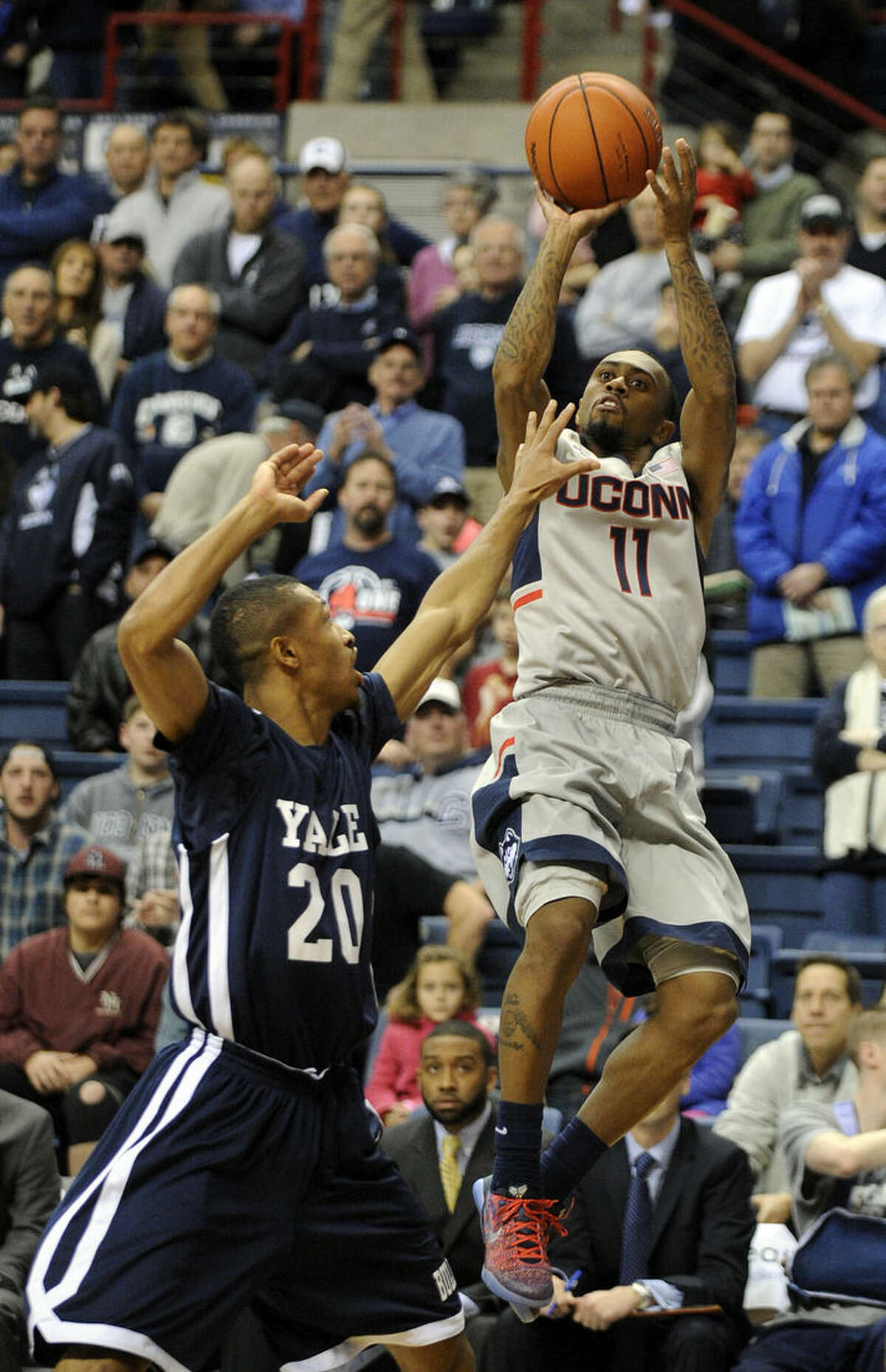 Connecticut's Ryan Boatright (11) shoots over Yale's Javier Duren (20) during the first half of an NCAA college basketball game in Storrs, Conn., on Sunday, Dec. 5, 2014. (AP Photo/Fred Beckham)