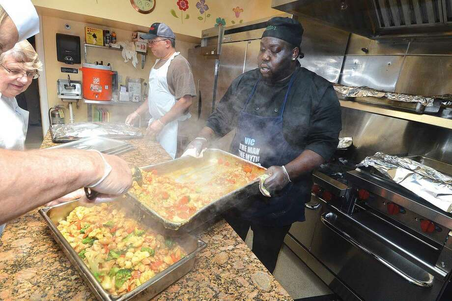 Hour Photo/Alex von Kleydorff Chef Victor Squire prepares Chicken Teriyaki, rice and fresh fruit for lunch in the new kitchen at The Open Door Shelter .