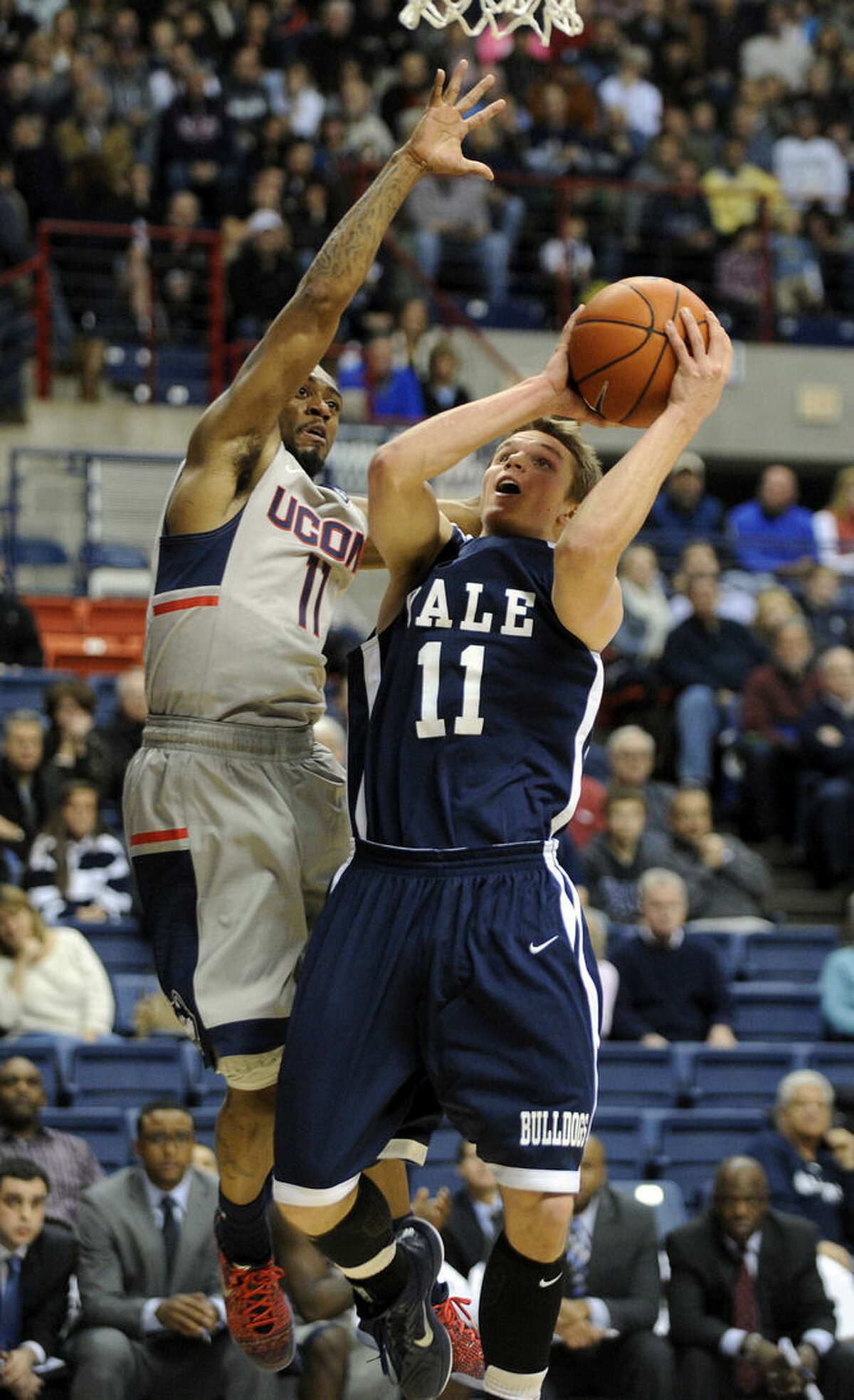 Yale's Makai Mason (11) drives past Connecticut's Ryan Boatright (11) during the first half of an NCAA college basketball game in Storrs, Conn., on Sunday, Dec. 5, 2014. (AP Photo/Fred Beckham)