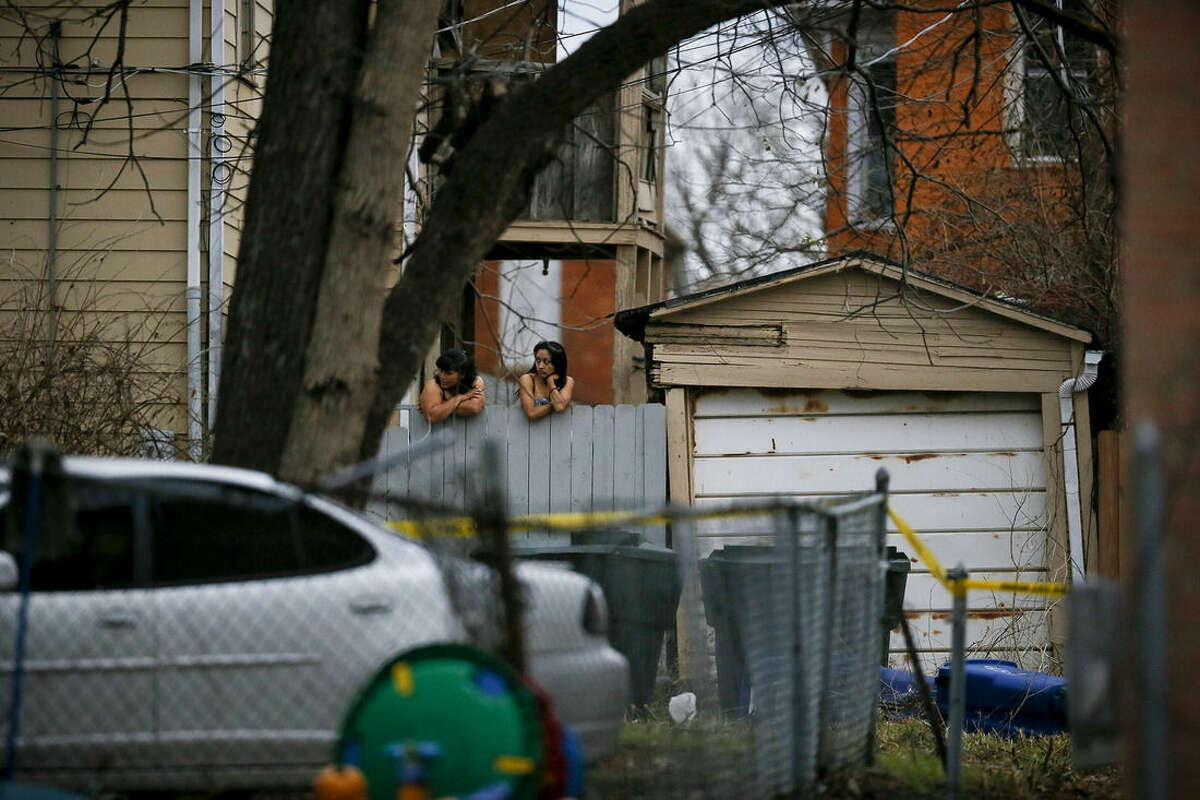 Neighbors observe police activity in an alley way near 6th Avenue and Cortland Avenue in Columbus, Ohio where the body of missing Ohio State football player, Kosta Karageorge was discovered in a dumpster on Nov. 30, 2014. According to police, Karageorge died of a self-inflicted gunshot wound. (AP Photo/The Columbus Dispatch, Kristen Zeis)