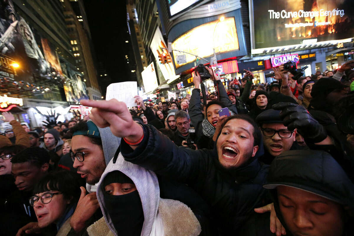 FILE - In this Dec. 4, 2014 file photo, protesters confront police and attempt to block traffic at the intersection of 42nd Street and Seventh Avenue near New York's Times Square, during a rally against a grand jury's decision not to indict the police officer involved in the death of Eric Garner. Officers say the outcry has left them feeling betrayed and demonized by everyone from the president and the mayor to throngs of protesters who scream at them on the street.