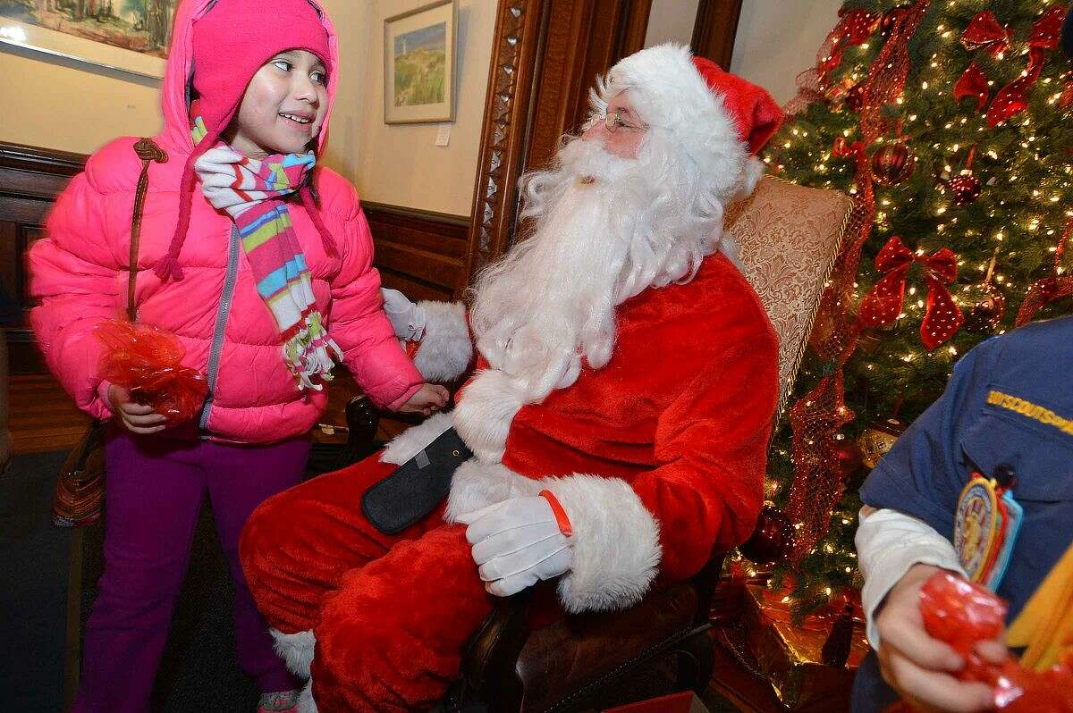 Hour Photo/Alex von Kleydorff 7yr old Lizzy Montenegro gets a goodie bag after she tells Santa her wish for Christmas during the City of Norwalk's Old Fashioned Tree Lighting Celebration at Lockwood-Mathews Park & Mansion