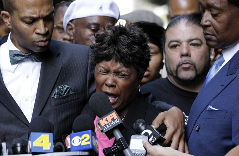 FILE- In this July 8, 2010 file photo, Wanda Johnson, center, mother of Oscar Grant, who was killed by transit officer Johannes Mehserle, speaks during a news conference in Los Angeles. Mehserle was convicted of involuntary manslaughter in the shooting death of, Oscar Grant, an unarmed man killed on an Oakland train platform in 2009. At least 400 people are killed by police officers in the United States every year, and while the circumstances of each case are different, one thing remains constant: In only a handful of instances do grand juries issue an indictment, concluding that the officer has committed a crime. (AP Photo/Jae C. Hong)