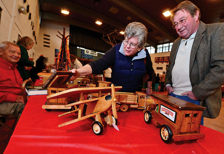 Hour photo / Erik Trautmann Jean and Jack O'Neil look over the handmade wooden toys by Fred Anderson for sale at the St. Ladislaus annual Christmas fair Saturday.