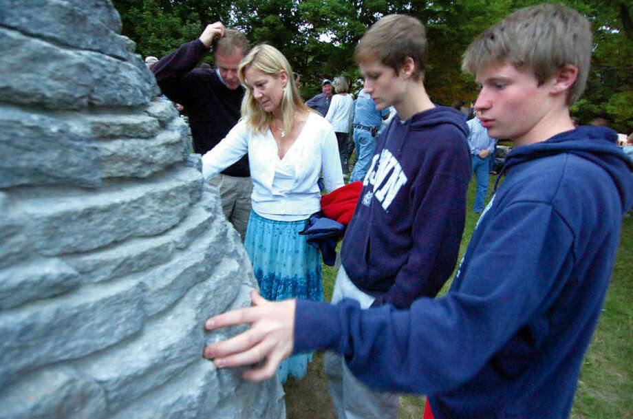 From left to right: Charlie Sandor and Alex Mirabile remember friend Nick Parisot during a memorial in 2013 near the Stone Cairn sculpture Father Rick Parisot built in a corner of a field at Millstone Farm in Wilton